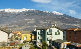 Residential buildings on foreground with majestic Italian alps in background, captured near Sondrio in Valtellina -. Residential buildings on foreground with Stock Photo