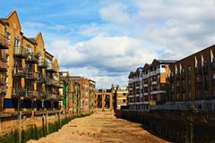 Residential buildings low tide armlet London England. Residential buildings along a dried  during the low tide armlet of Thames River,Poplar London United Royalty Free Stock Photography