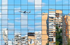 Residential buildings and plane are reflected in the wind stock photo