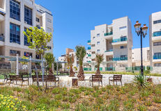Residential buildings and small square in Ashqelon, Israel. Small city square with palms and benches near complex of contemporary residential buildings in Royalty Free Stock Photo