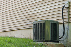 Residential Central Air Conditioner Unit. A residential central air conditioning unit sitting outside a home used for regulating the homes AC to a comfortable Royalty Free Stock Photo