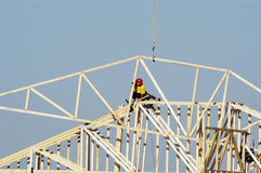 Residential Construction 3. Workers move a roof truss into position on a new house under construction in a suburban neighborhood Stock Photography