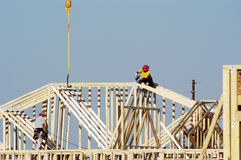 Residential Construction 5. Workers move a roof truss into position on a new house under construction in a suburban neighborhood Stock Image