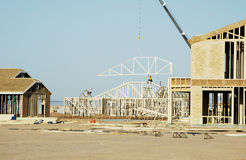Residential Construction. Workers move a roof truss into position on a new house under construction in a new neighborhood Stock Photo