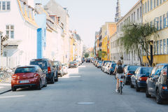 Residential Copenhagen street. Girl cycles down a residential backstreet in Copenhagen, Denmark. 7 May 2016 Royalty Free Stock Photo
