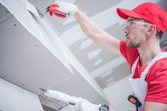 Residential Drywall Patching. Residential Remodeling Drywall Patching. Caucasian Contractor in His 30s. Construction Theme Stock Images