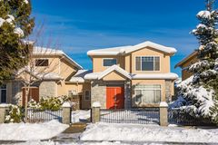 Residential duplex house with front yard in snow on winter sunny day in Canada. Residential duplex house with front yard in snow. North American family duplex royalty free stock images
