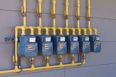 Residential gas energy meters row supply plumbing. Row of residential natural gas meters and yellow pipe plumbing on exterior wall to measure household energy Stock Photos