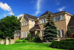 Residential home. Large upscale residential home with bright green lawn and blue sky Stock Image