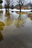 House, Home Flooding From Winter Snow Melt. A residential home is in danger of property damage from flooding caused by high water and snow melt. Many houses and Royalty Free Stock Photos