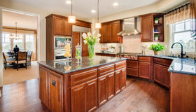 Residential Model Home Kitchen and Dining Room. Residential home kitchen with dining room in the background.  Natural wood cabinets.  Wood floor.  Granite Stock Photos