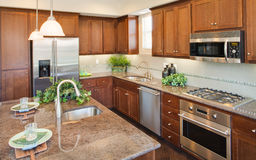 Residential Model Home Kitchen. Residential home kitchen.  Natural wood cabinets.  Granite counters.  Stainless steel appliances including  microwave oven Stock Image