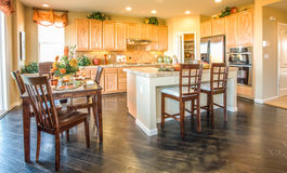 Residential Home Kitchen and Nook. Residential home kitchen and dining nook.  Wood floors. Tile island and counters.  Wood bar chairs.  Wood nook table and Stock Photos