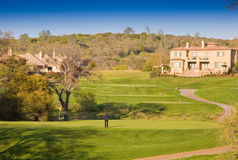 Residential homes on a hilly golf course. Upscale estate style homes on a hilly golf course.  Oak trees and blue sky in background.  Homes are located in Stock Photos