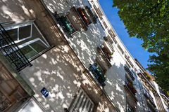 Residential house with leaves. Common house in Paris, France with some shadow cast by the branches and leaves stock photo