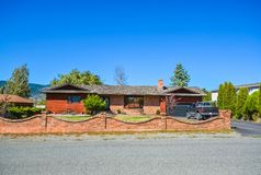 Residential house with red brick wall with black truck parked on driveway. Red brick built residential house with red brick wall on front yard. Family house with stock images
