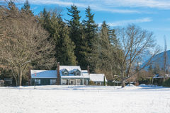 Residential house in snow on a sunny day. Big farmers house with spacious front yard at winter season. Residential house in snow on a sunny day Stock Image