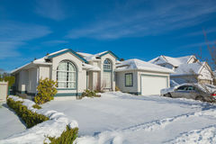 Residential house in snow on sunny winter day. Big luxury house with parked car on driveway and front yard in snow. Residential house on sunny winter day Stock Images