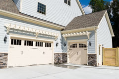 Residential house three car garage doors. Driveway Royalty Free Stock Photography