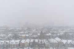 Residential houses and roofs covered with snow in winter snowsto. View from above on residential houses and roofs covered with snow during winter snow storm in stock photography