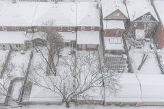 Residential houses and roofs covered with snow in winter snowsto. View from above on residential houses and roofs covered with snow during winter snow storm in royalty free stock image