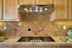 Residential kitchen cooking area. Kitchen cooktop, counter, hood and cabinets Stock Photography