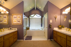 Residential Master Bath Room. Master bath room with carpet and white tiles, large bath tub, glass shower door, his and hers sinks and counters, wood cabinets and Royalty Free Stock Photo