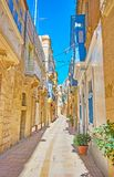 The residential quarter of Birgu, Malta. Walk the narrow street of historical residential quarter with preserved old edifices of native limestone with wooden royalty free stock images
