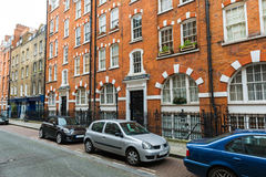 Residential street. London street with row of old bricked residential buildings Stock Photos