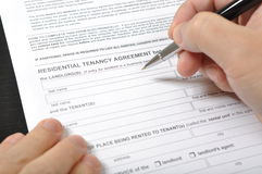Residential tenancy agreement. Man signing a rental contract Stock Photos