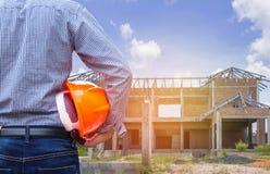 Residentingenieur, der gelben Schutzhelm am neuen Wohnungsbau hält Lizenzfreies Stockfoto