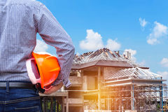 Residentingenieur, der gelben Schutzhelm am neuen Wohnungsbau hält Stockbilder