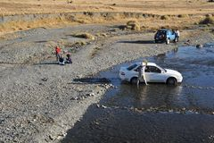 Residents of La Paz wash their cars in a mountain river in urban area. Royalty Free Stock Images