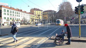 Residents of Milan crossing the road near the tram stop. Milan City transport. stock video footage