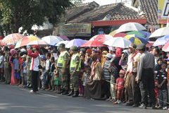 Residents use the umbrella to see the parade in Sukoharjo Stock Images
