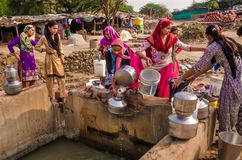 Residents of village Makarba collect water from a water supply nearby well. royalty free stock photo