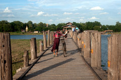 Residents and visitors traveling on the U-bein Bridge,Myanmar. Stock Photography