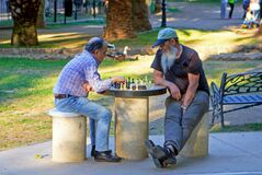 Nice weather to play a game of chess in the park in the evening.