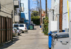 Residing in Venice Beach. Venice Beach, USA - June 4, 2014: A residential street with trash cans on the roadside, parked cars and power poles with wires above Royalty Free Stock Images