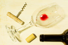 Residue of red wine. Unfinished red wine in the glass on the table with a corkscrew and cork Stock Images
