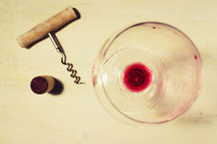 Residue of red wine. Unfinished red wine in the glass on the table with a corkscrew and cork Royalty Free Stock Image