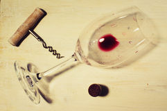 Residue of red wine. Unfinished red wine in the glass on the table with a corkscrew and cork Royalty Free Stock Photo