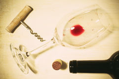 Residue of red wine. Unfinished red wine in the glass on the table with a corkscrew and cork Stock Photo