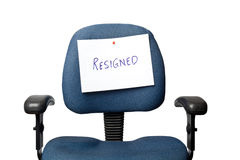 Resigned. Office chair with a RESIGNED sign isolated on white background Royalty Free Stock Image