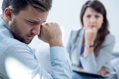 Resigned man at psychiatrist's office. Resigned men receiving psychotherapy at psychiatrist's office Royalty Free Stock Photos