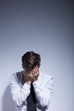 Resigned and overwhelmed. Shot of a man standing against a white wall and covering his face Royalty Free Stock Photos