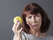 Resigned 50s woman with symbol of healthy lifestyle and fresh food Royalty Free Stock Photography