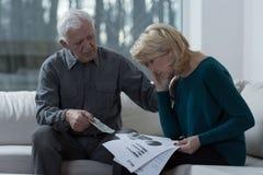 Resigned woman analyzing unpaid bills. Resigned women analyzing unpaid bills with her supporting husband Stock Image