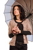 Resigned woman watching the rain. Beautiful resigned woman with a patient expression standing sheltering under her umbrella looking up at the sky watching the Stock Photography