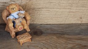 Resin teddy bear sitting in a chair on a wooden background royalty free stock photos